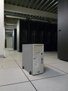 The single computer providing the Manchester grid site in 2001. In the background are the 40 racks of 1000 computers which had replaced it by 2005.